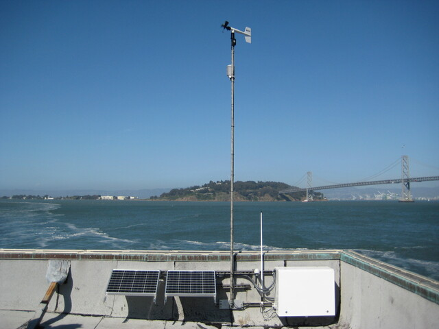 A cluster of meteorological measurement instruments atop a tower overlooking the ocean.